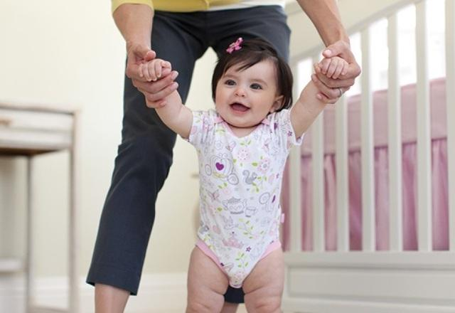 ребенок ходит, держась за пальцы взрослого