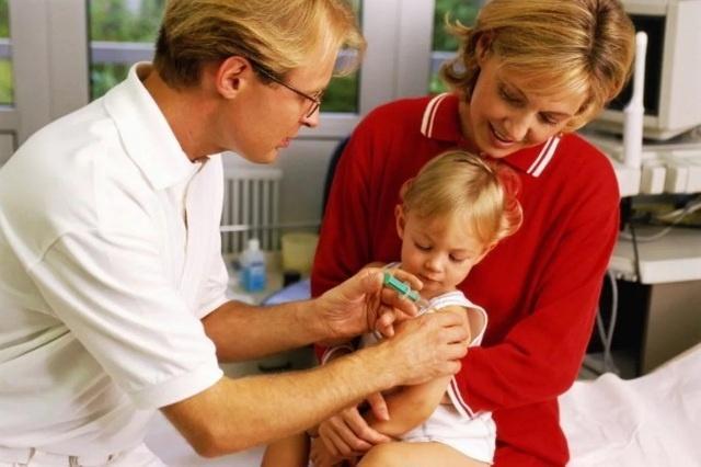 на руках у мамы во время прививки