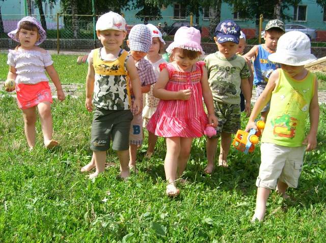 дети гуляют по траве босиком